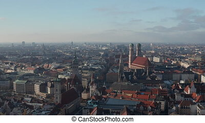The Famous German Cathedrals Frauenkirche, Marienkirche and St. Peter's Church in City Center of Munich, Germany with View of Marienplatz, Aerial Dolly slide right 4K
