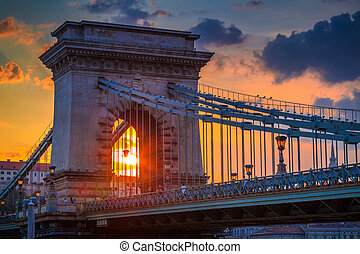 The famous Szechenyi Chain Bridge in Budapest above the Danube river, with sky illuminated by sunset, Hungary, Europe.