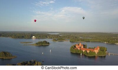 The famous Trakai castle on an island in the middle of Lake Galve, surrounded by trees. Shooting the sky from a height in which a pair of large balloons are visible. Landmark in Lithuania, Vilnius.