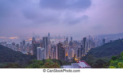 The famous view of Hong Kong from Victoria Peak night to day timelapse. Taken before sunrise with colorful clouds over Kowloon Bay.