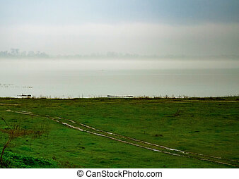 The far bank of the river is lost in the fog
