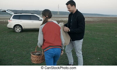The father and daughter collect litter, a basket, go to the...