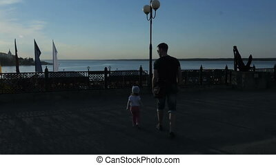 The father and his little daughter are holding hands along the embankment. Slow motion