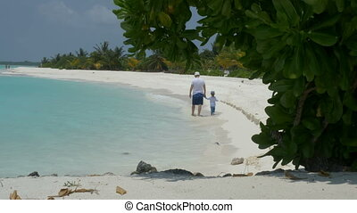The father and his little daughter walk along a tropical beach with white sand.