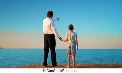 The father and son stand, by the hand, on the seashore, father points his finger into the distance