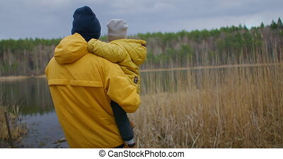 The father holds his son in his arms and looks at the lake together. Family closeness of father and child. Fatherhood and lifestyle in an authentic environment of nature