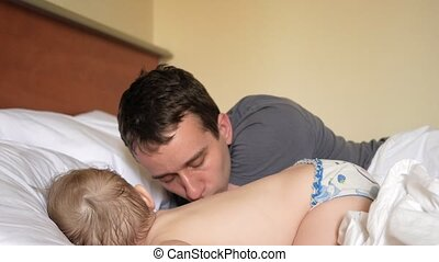 The father kisses the son who sleeps in the bed. The baby is less than two years old.