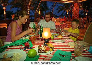The father, mother and the son have supper