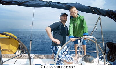 The father teaches his son to steer the yacht. Young Captain