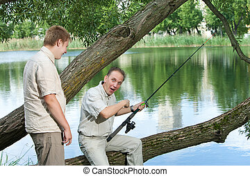 The father with the son on fishing. Rejoice to a biting
