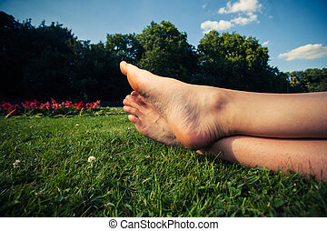 The feet of a young woman on the grass in a park