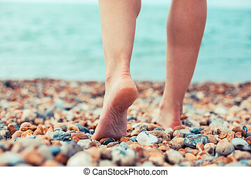 The feet of a young woman standing on the beach - THe feet...