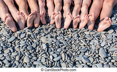 The feet of children on the beach.