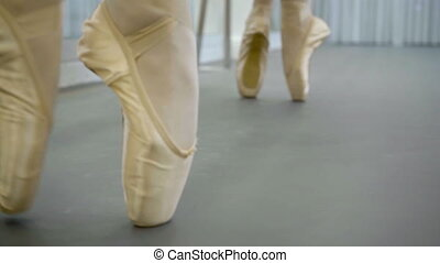 The feet of two ballerinas in silk pointe doing pour be...