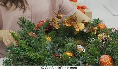 The female designer decorates the Cristmas wreath in the studio.