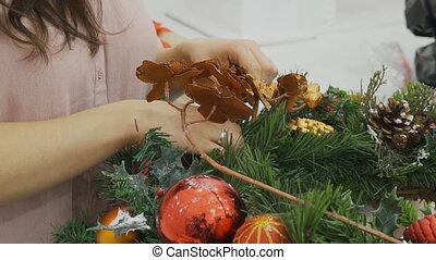 The female designer makes a wreath with imitative fir...