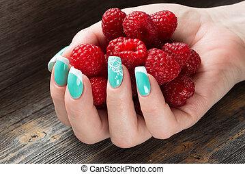 The female hand holds a handful of ripe berries raspberry...