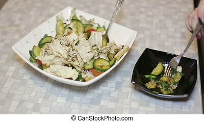 The female hand puts a salad of fresh vegetables in a bowl...