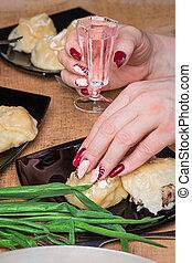 The female hand with beautiful manicure keeps a shot glass...