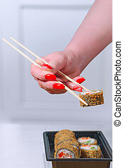 The female hand with magnificent manicure takes sushi from a...