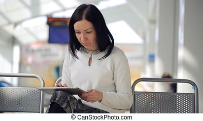 The female is working with phone waiting in airport hall sitting