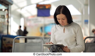 The female is working with tablet pc waiting in airport hall...