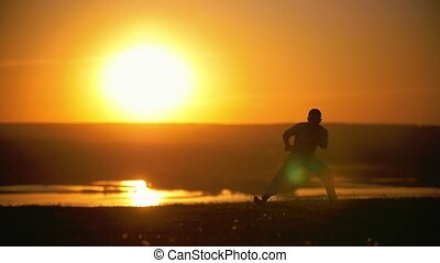 The fighter makes a handstand on the background of the setting sun, slow-motion
