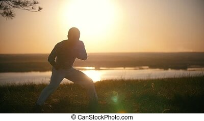 The fighter makes kicks of legs in a turn on the background of the setting sun, slow-motion