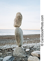 The figure of stones standing on each other, on the beach against the sea.
