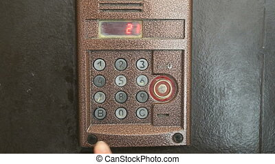 the finger dials the number of the apartment old intercom system