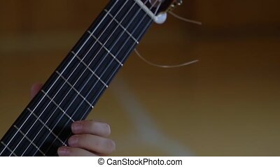 The fingers of a young man clamp the strings of a classical guitar
