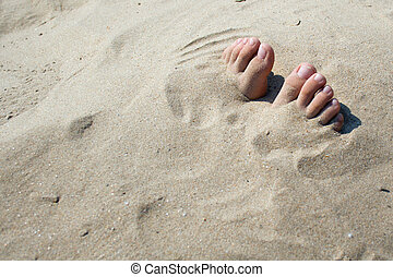 The fingers of feet which are sticking out of sand
