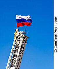 The firefighter secures a Russian flag on the fire ladder on background of blue sky