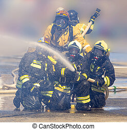 The firefighters with hose extinguish a fire