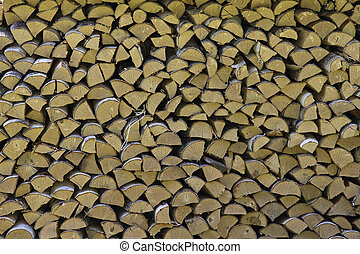 The firewood is stacked in a woodpile. Decorative wall of firewood