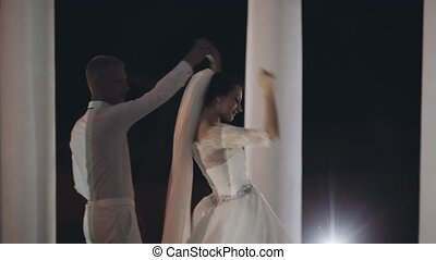 The first dance of loving newlyweds in the evening. Beautiful couple hold hands and turn around, happy wedding day.