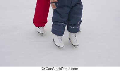 The first steps of a small child on ice skating. Mom teaches skating and holds his child on the ice. Active lifestyle
