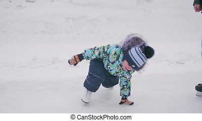 The first steps of a young child on skates. Boy on skates...