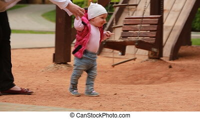 The first steps of little cute baby-girl on the playground in the city park.