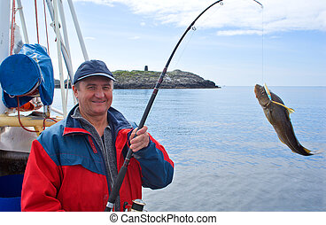 The fisherman on the boat in Norwegian fjord - The fisherman...