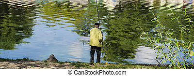 The fisherman stay a back on the bank of river with fishing tackles