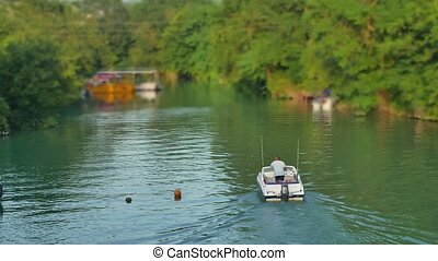 The fisherman swims on a boat on the river water. Man fishing summer river nature