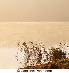 The fishermen on the boat in the fog. Fishermen in the morning mist