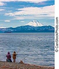 fishermen with fishing rod on coast of Pacific ocean in the background of the volcano