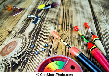 The fishing accsessories composition on the wooden table
