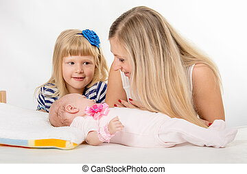 The five-year girl is looking at her mother who is looking at newborn daughter