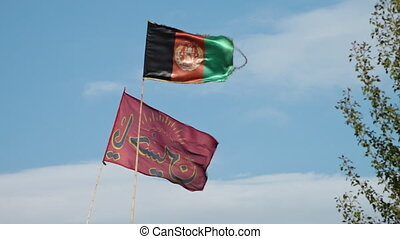 A hand held, low angle, medium shot of the flag of Afghanistan and another red Muslim flag moving in the windy day.