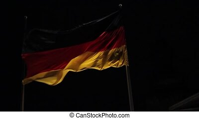 The flag of Germany develops against the background of the...