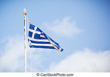The flag of Greece over blue sky.