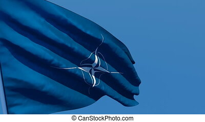 The flag of NATO flutters in the wind against a blue sky